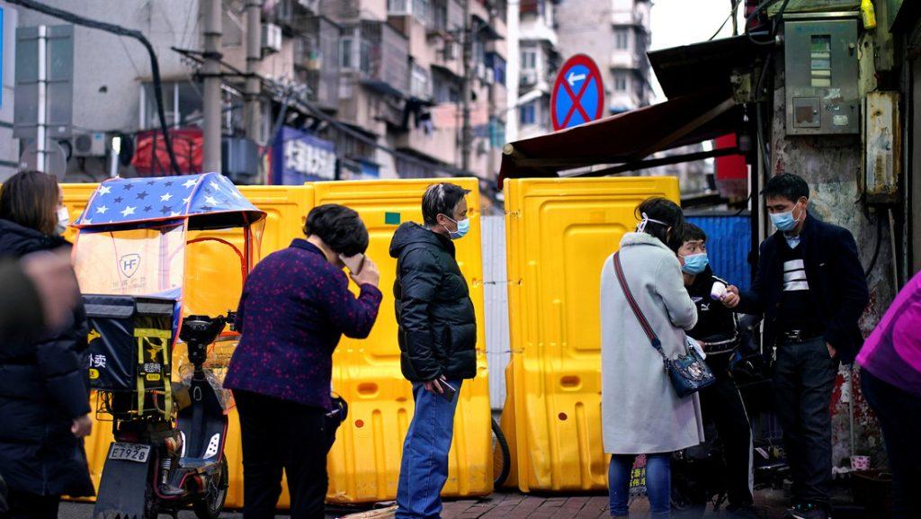 Personas con mascarillas en Wuhan, China, 28 de marzo de 2020.