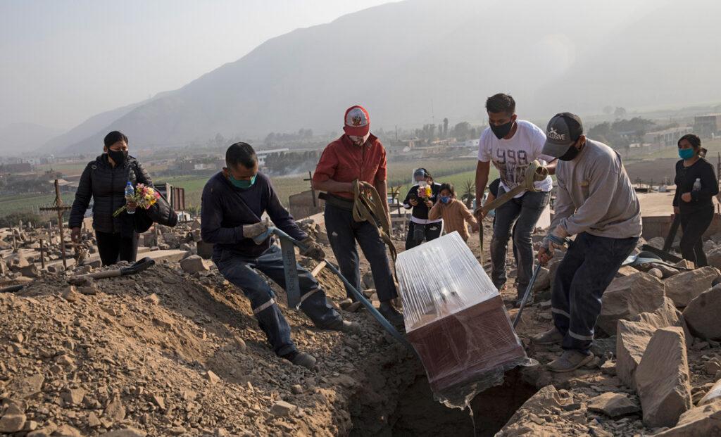 Trabajadores y familiares colocan un ataúd que contiene el cuerpo de Manuel Sánchez, de 38 años, en un cementerio en Carabayllo, Lima, Perú, el jueves 13 de agosto de 2020.