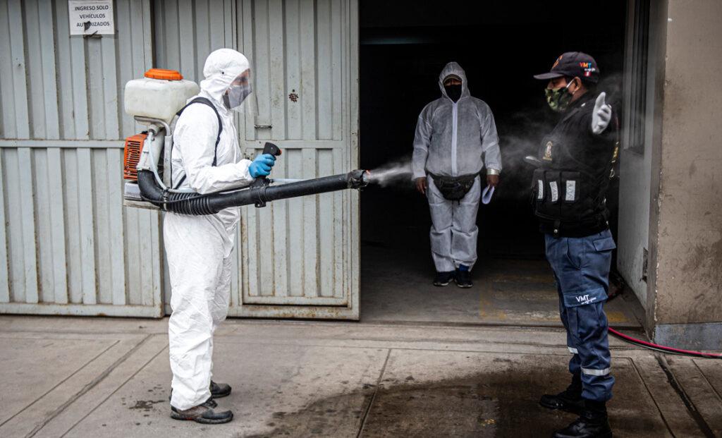 Un trabajador municipal desinfecta a un guardia de seguridad en Villa María del Triunfo, en la periferia sur de Lima, el 29 de julio de 2020.