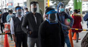 Viajeros con máscaras protectoras y escudos faciales esperan para ingresar a una estación de tren en Lima, Perú, el sábado 25 de julio de 2020.