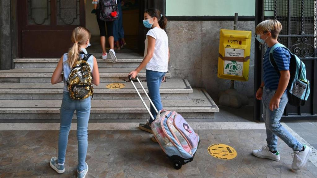 Estudiantes con máscaras llegan el 14 de septiembre para el inicio del año escolar en la escuela secundaria técnica Luigi Einaudi en Roma, Italia.