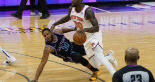 El jugador de los Knicks de Nueva York Julius Randle (derecha) recibe una falta de Glenn Robinson III de los Kings de Sacramento, en el juego de la NBA que enfrentó a ambos equipos, en Sacramento, California, el 22 de enero de 2021. (AP/Rich Pedroncelli)