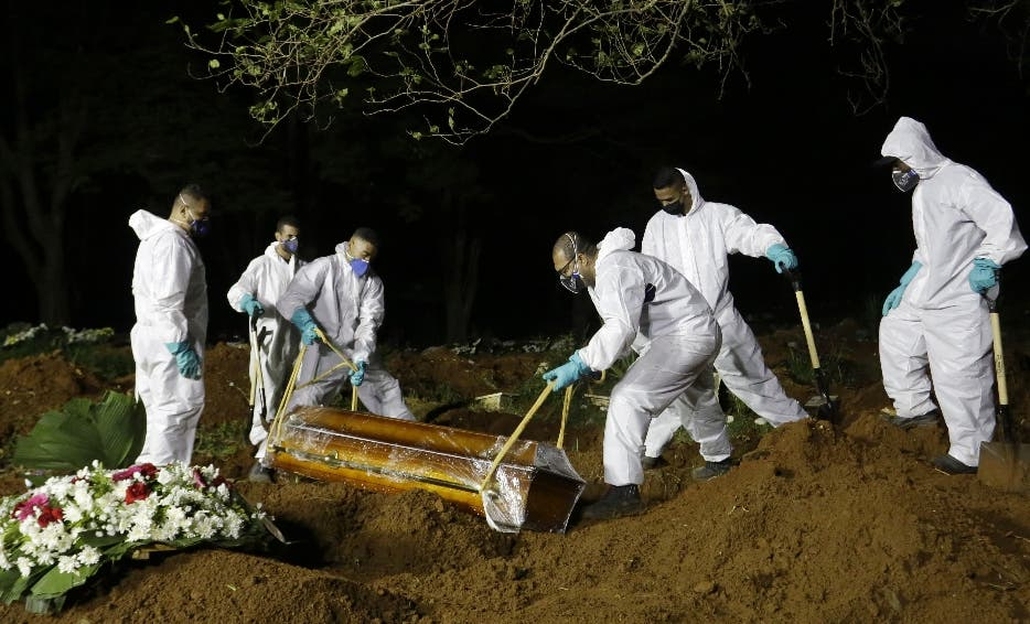 Cemetery workers lower the coffin of a COVID-19 victim into his grave at the Vila Formosa cemetery in Sao Paulo, Brazil, late Wednesday, March 31, 2021. Because of the increased number of deaths in the city, the burial service in some public cemeteries has been extended to the hours of the night. (AP Photo/Nelson Antoine)